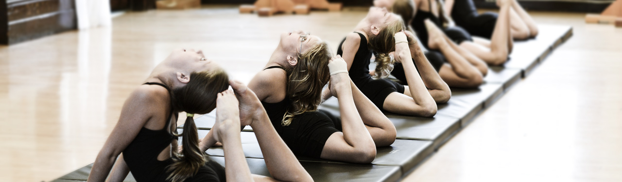 Young girls in an acro dance class lay in a line with their feet touching the back of their heads